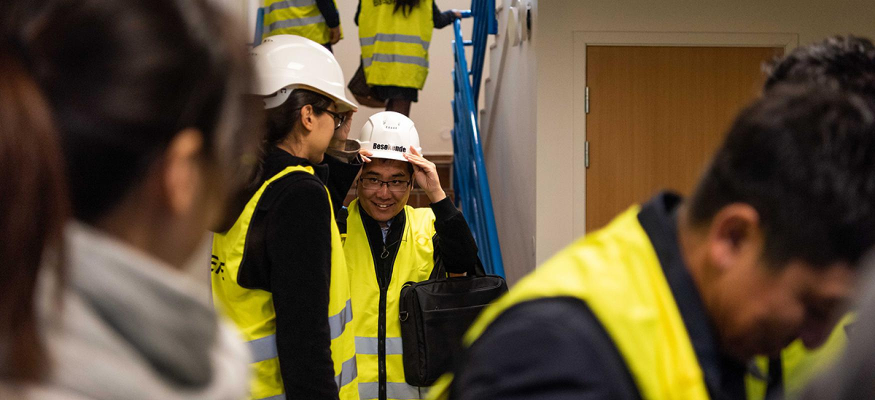 A Chinese delegation wearing yellow vests and hard hats at a sight visit in Norway.