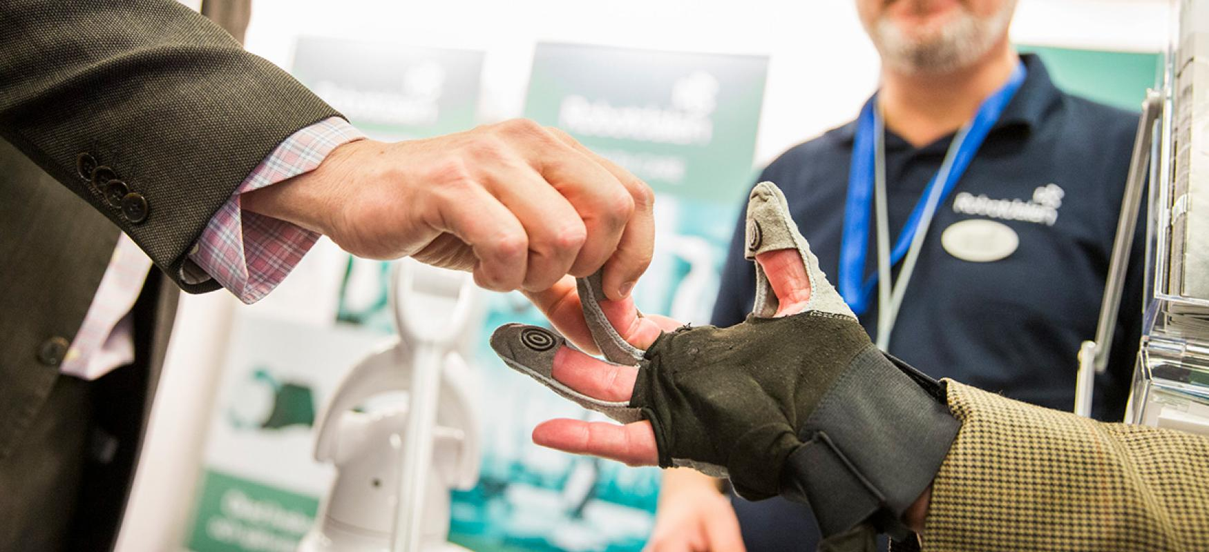 Man testing a health technology device in the form of a glove at Vitalis 2018.