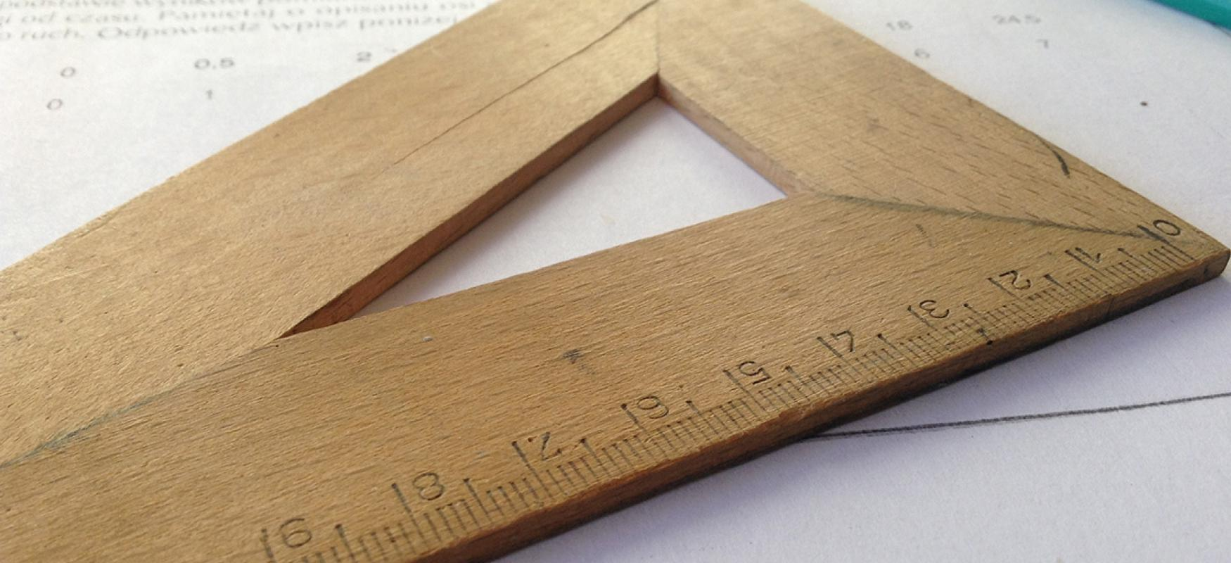 A wooden triangle ruler lying on top of handwritten notes.