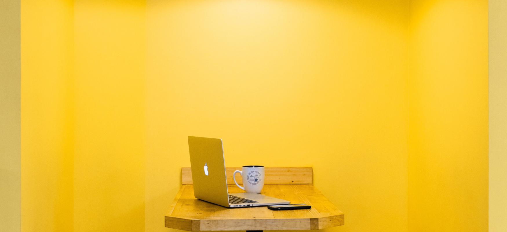 Booth with two benches and a table with a laptop on top. Yellow wall.