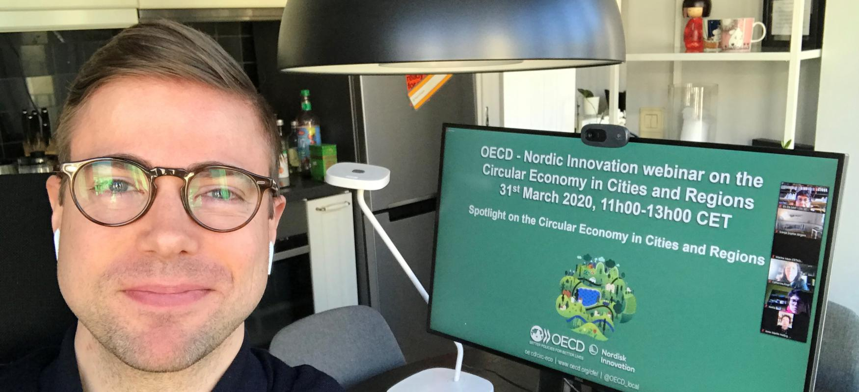 Senior innovation adviser at Nordic Innovation, Elis benediktsson in front of a computer screen displaying an image of the OECD and Nordic Innovation webinar 31 march 2020