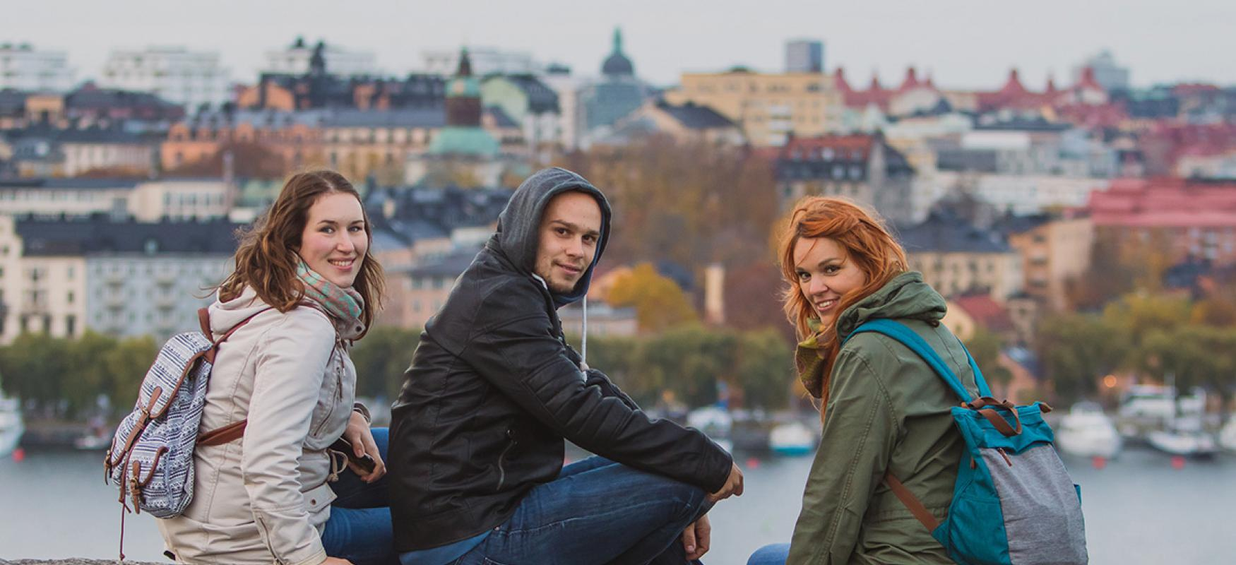 Young people hanging out on a rock with Stockholm in the background.