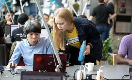 Two people in front of a laptop at a hackathon in Helsinki.