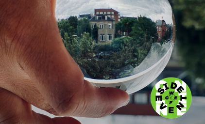 Person holding glass globe with reflecting building and trees in the background. WCEFonline sideevent logo